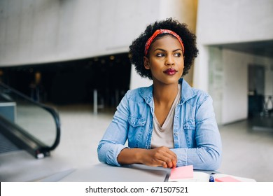 Young African female entrepreneur working at a table in a modern office building lobby looking deep in thought