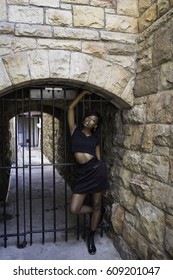 A young African female poses in front of a closed tunnel's gate