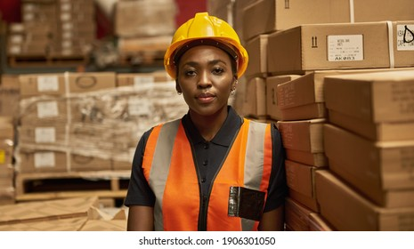 Young African female warehouse worker wearing a safety vest and helmet leaning against a stack of boxes