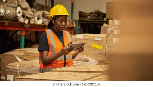Young African female warehouse worker working on a digital table during an iventory check
