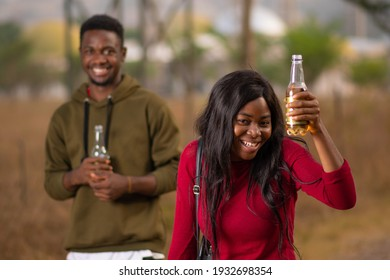 young african friends holding drinks in bottles at an outdoor party