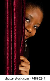 Young African Ghanese woman hiding shy behind a curtain