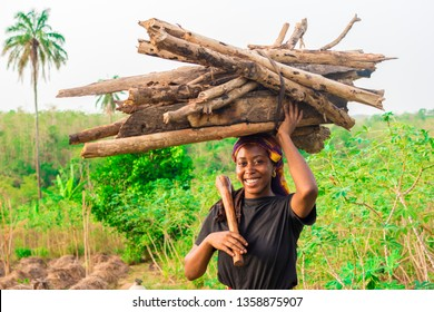 young African girl carrying wood and a hoe smiling on a farm