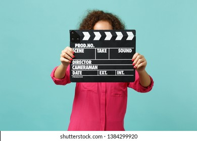 Young african girl in casual clothes covering face with classic black film making clapperboard isolated on blue turquoise background. People sincere emotions, lifestyle concept. Mock up copy space