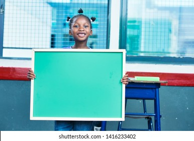Young african girl at school holding chalkboard.