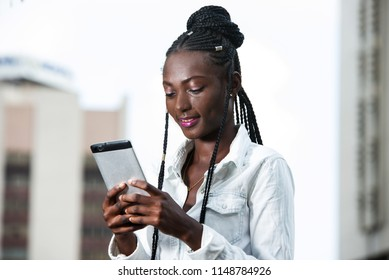 young african girl standing in white shirt looking at mobile phone while smiling.