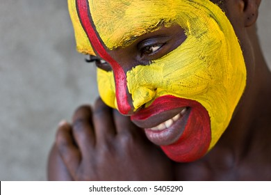 Young African girl, tribal painted face in yellow and red
