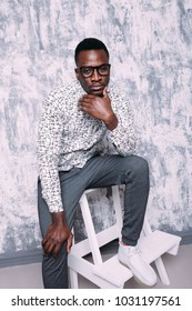 young African guy student with glasses. street style in clothes: wide pants and shirt. emotional portrait of a teenager. clean leather and short hair