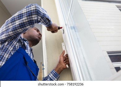 Young African Handyman In Uniform Fixing Glass Window With Screwdriver