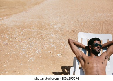 young african happy man wearing sunglasses lying on ocean shore and enjoying summer holiday