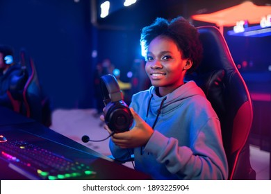 Young african happy woman professional gamer in online video game with headphones, neon background.