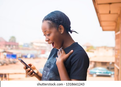 young African lady browsing with her mobile phone with surprised on her face
