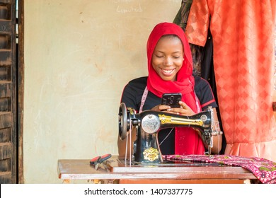 young African lady tailor smiling while using her phone