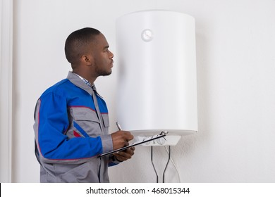 Young African Male Plumber Holding Clipboard Looking At Electric Boiler
