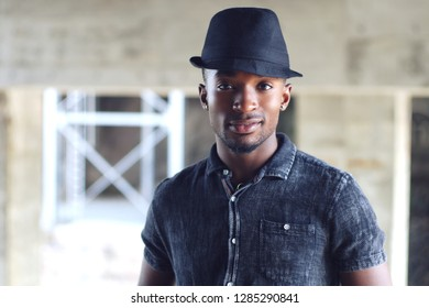 young african man black hat gray shirt outside portrait