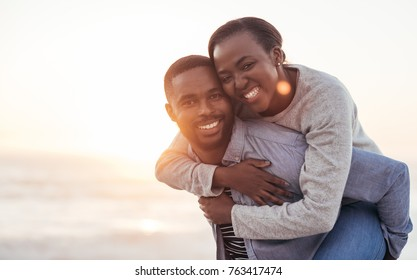 Young African man carrying his smiling girlfriend on his back while enjoying a late afternoon together at the beach