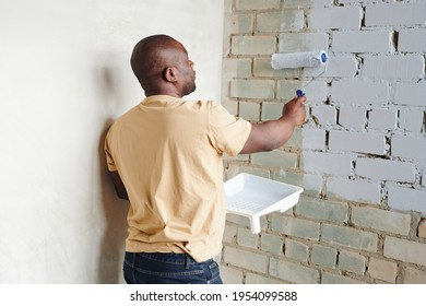 Young African man in casualwear holding paintroller while standing by corner in front of brick wall and painting it into white color