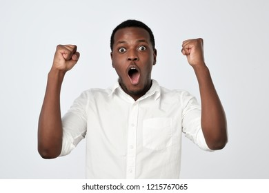 Young african man celebrating victory over gray background. I can not believe my luck