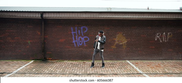 Young African man dancing near the wall with Hip Hop graffiti. Horizontal outdoors shot.