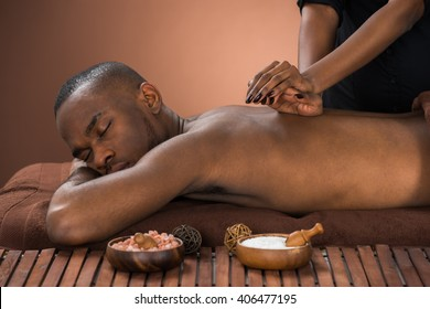 Young African Man Getting Massage In Spa