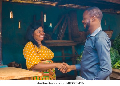 young African man handshaking a market woman after a successful business transaction