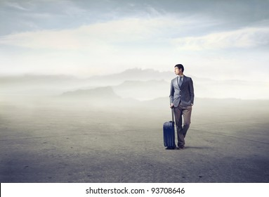 Young african man holding a suitcase in a desert