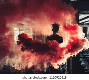 Young African man in jeans stands in water under bridge and holds colored red smoke bomb in his hands on background of concrete supports. With backlight.