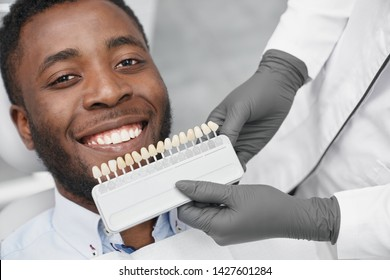 Young african man looking at camera and smiling while female dentist keeping range of fillings in clinic. Happy patient enjoying white beautiful smile while visiting dentist office. Concept of cure.