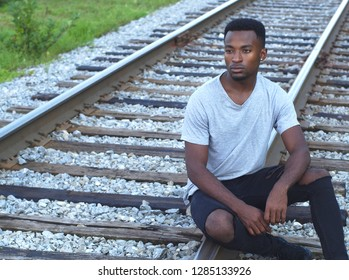 young african man portrait sitting on railroad rail train track