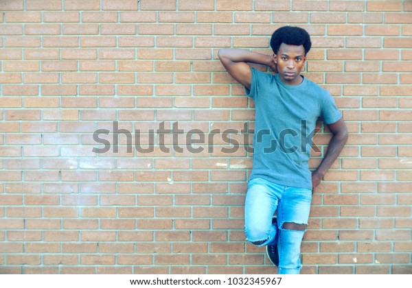 young african man posing on brick wall handsome guy jeans
