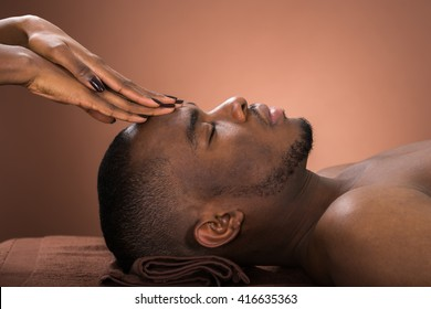 Young African Man Receiving Forehead Massage In Spa