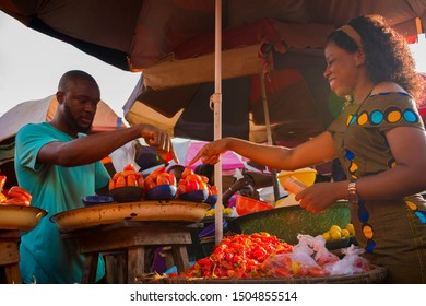young African man selling some tomatoes to a beautiful African woman in the market
