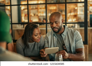 Young African man showing his friend pictures on a cellphone while sitting together with friends in a bar