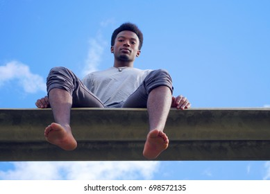 young african man sitting barefoot blue sky gray t-shirt low angle view