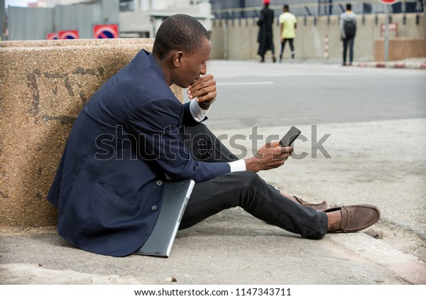 young african man sitting in a suit looking at mobile phone.