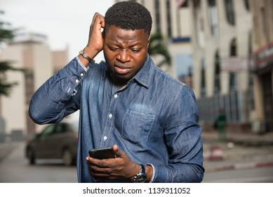 young african man standing in jeans shirt going to look at mobile phone with strange air.