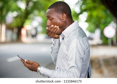 young african man standing in shirt looking at phone hiding mouth with hand.