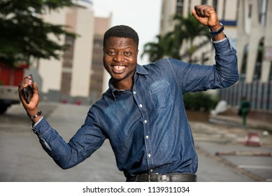young african man standing in the street in jeans shirt looking at the camera smiling with closed fist.
