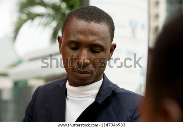young african man standing in a suit looking at something.