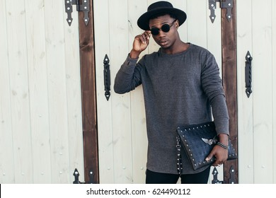Young african man in sunglasses and hat near a wall