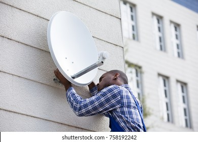 Young African Man In Uniform Fitting TV Satellite Dish On Wall