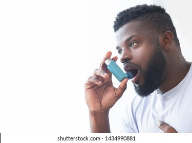 Young african man using asthma inhaler at home. Modern generation sickness, empty space