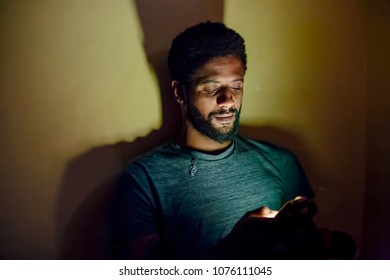 Young african man using mobile phone in dark room