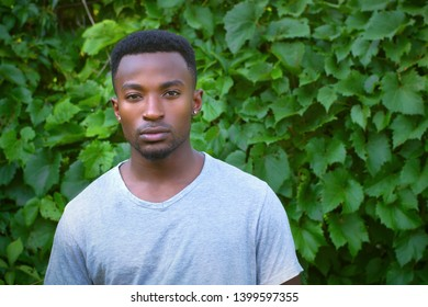 young african man vine leafs background outdoor portrait
