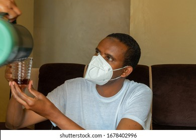young african man wearing face mask and holding up a cup that is being filled with tea. concept of self isolation . people must follow heed advice of healthcare professionals to stop spread of covid19