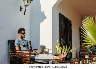 Young african man wearing glasses using laptop at home. Freelance worker, freedom and enjoy summer day