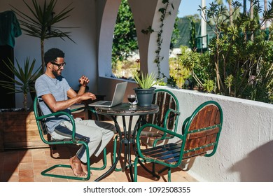 Young african man wearing glasses using laptop at home, communicate with friends, have fun, laughing and typing