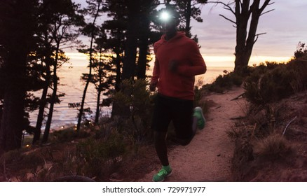 Young African man wearing a headlamp running alone down a trail in the forest while out for a cross country run at dusk