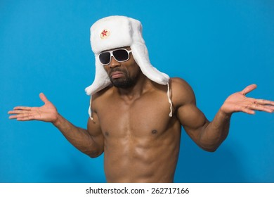 young African man in white fur hat with red star is puzzled on blue background