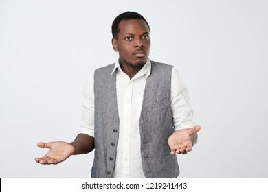 Young african man in white shirt being at a loss, showing helpless gesture with arm and hands, mouth curved as if he does not know what to do. Why did I fail my job.